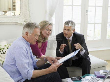 Photo pour Couple de personnes âgées assis sur le canapé avec le conseiller financier, vue - image libre de droit