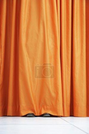 Person hiding behind curtain