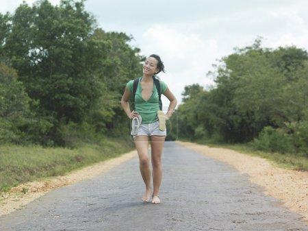 Woman barefoot walking on rural road