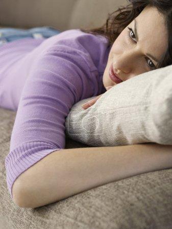 Photo pour Belle femme se détendre sur le canapé - image libre de droit