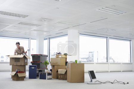 Photo for Woman with Cardboard Boxes in Empty Office Space - Royalty Free Image
