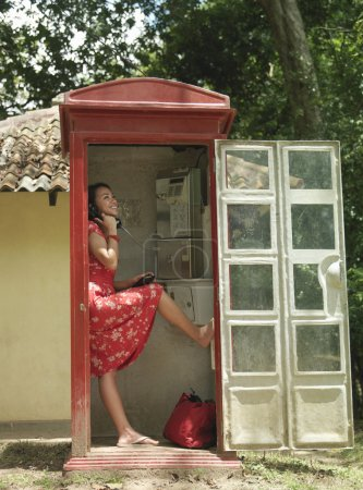 Young woman in telephone box