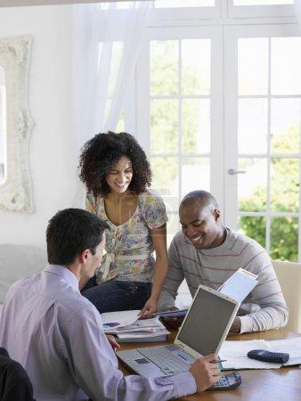 Photo pour Young African American couple finances maison discuter avec un conseiller financier à la table de salle à manger - image libre de droit