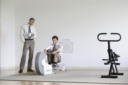 Businessman using rowing machine with colleague