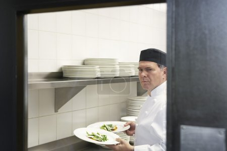 Man with plates in kitchen