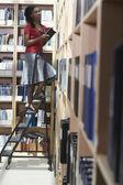 female office worker standing on ladder