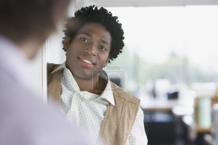 Businessman talking to blurred colleague in office