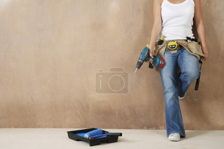 Woman with toolbelt and drill