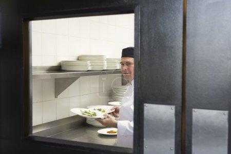 Man chef holding plates