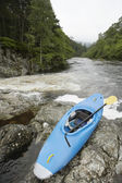 Blue kayak by river