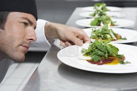 Male chef preparing salad