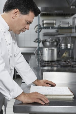 Chef reading recipe book