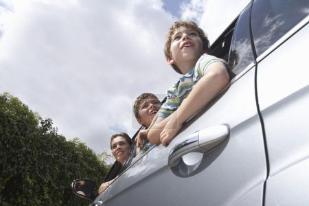 Mother and boys leaning out car window