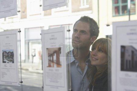 Photo pour Couple à la recherche dans la fenêtre de l'Agent immobilier - image libre de droit
