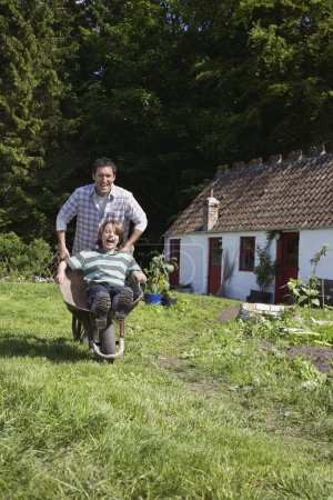 Father and son in wheelbarrow