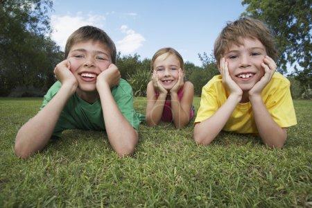 Photo pour Deux garçons et une fille couchés sur l'herbe appuyé sur les coudes - image libre de droit