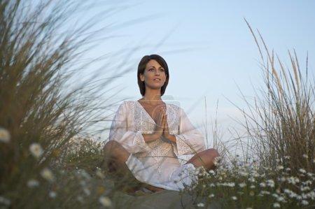 Photo pour Femme pratiquant le yoga sur les dunes de plage - image libre de droit