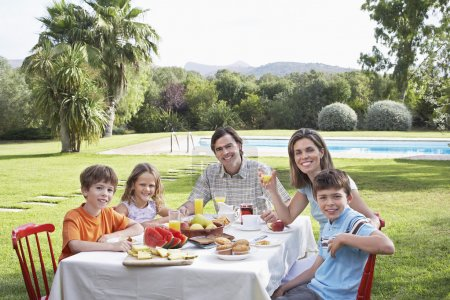 Family with three children  sitting at table
