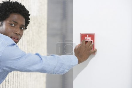 Businessman starting fire alarm