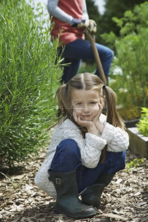 Girl in garden with working mother
