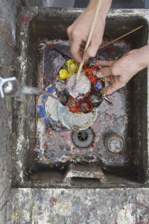 Photo for Artist rinsing palette at sink in studio, view from above, close-up of hands - Royalty Free Image