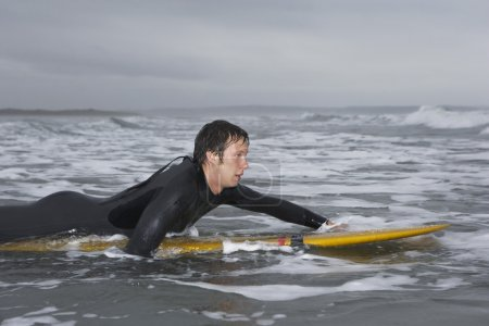Surfer puddling on surfboard