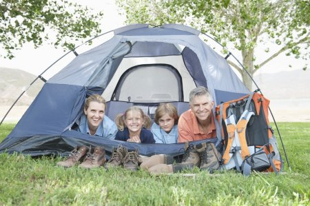 Family smiling from a tent
