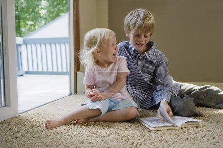 Siblings sitting on carpet with book