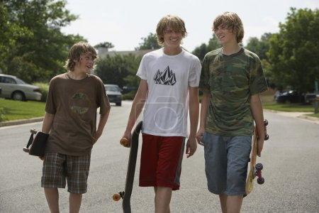 Brothers walking on street carrying skateboards