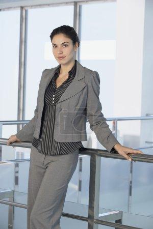 Photo pour Femme d'affaires debout contre balustrade dans un immeuble de bureaux, portrait - image libre de droit