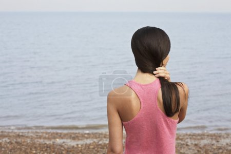 Photo pour Jeune femme debout sur la plage, vue arrière - image libre de droit