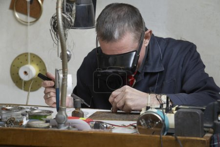 Clockmaker working in workshop
