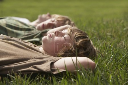 Three teenage brothers  on grass
