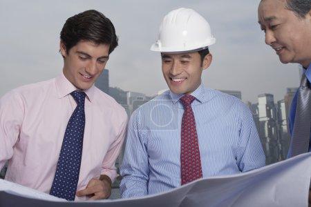Businessmen reading blueprints