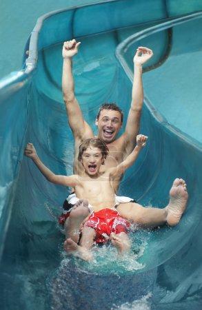 Photo pour Père et fils avec les bras tendus sur toboggan aquatique - image libre de droit