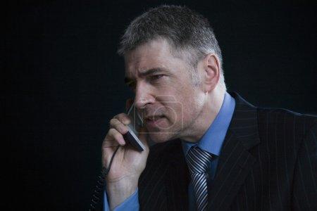 Businessman using landline phone