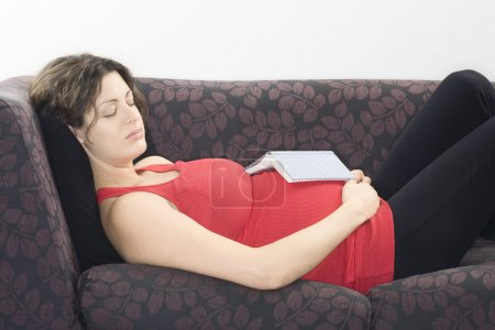 Pregnant woman with book sleeping