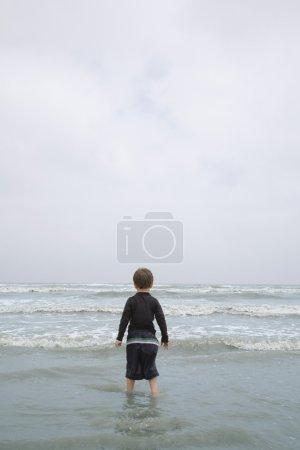 Photo pour Jeune garçon debout sur la plage - image libre de droit