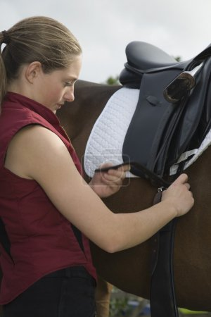 Girl tightening saddle