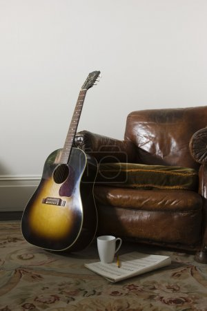 Armchair and guitar in room