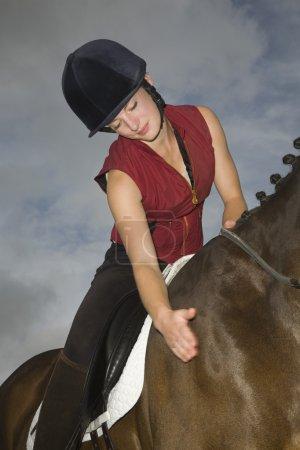 horseback rider stroking horse