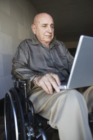 Photo for Elderly man in wheelchair using laptop - Royalty Free Image