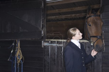 horseback rider with horse in stable