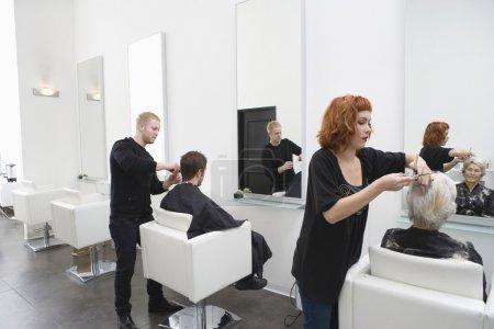 Stylists cut clients' hair in unisex salon