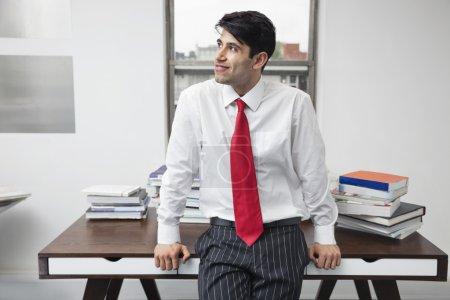 Foto de Hombre de negocios indio apoyado en el escritorio mientras mira hacia otro lado en la oficina - Imagen libre de derechos