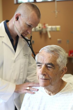 Young doctor listens to young elderly man's breathing