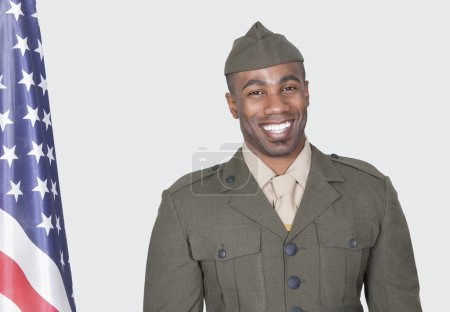 Photo for Portrait of a male US soldier smiling with American flag over gray background - Royalty Free Image