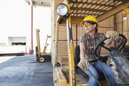 Photo pour Travailleuse industrielle regardant ailleurs tout en conduisant un chariot élévateur - image libre de droit