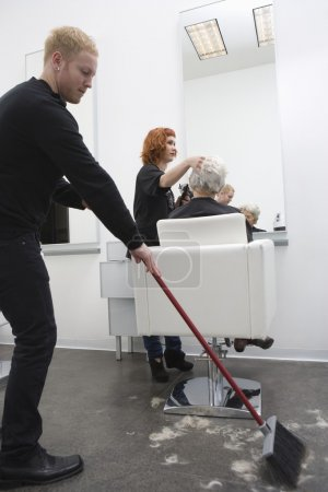 Hairdressing assistant sweeps up