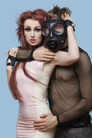 Man in gas mask embracing funky woman